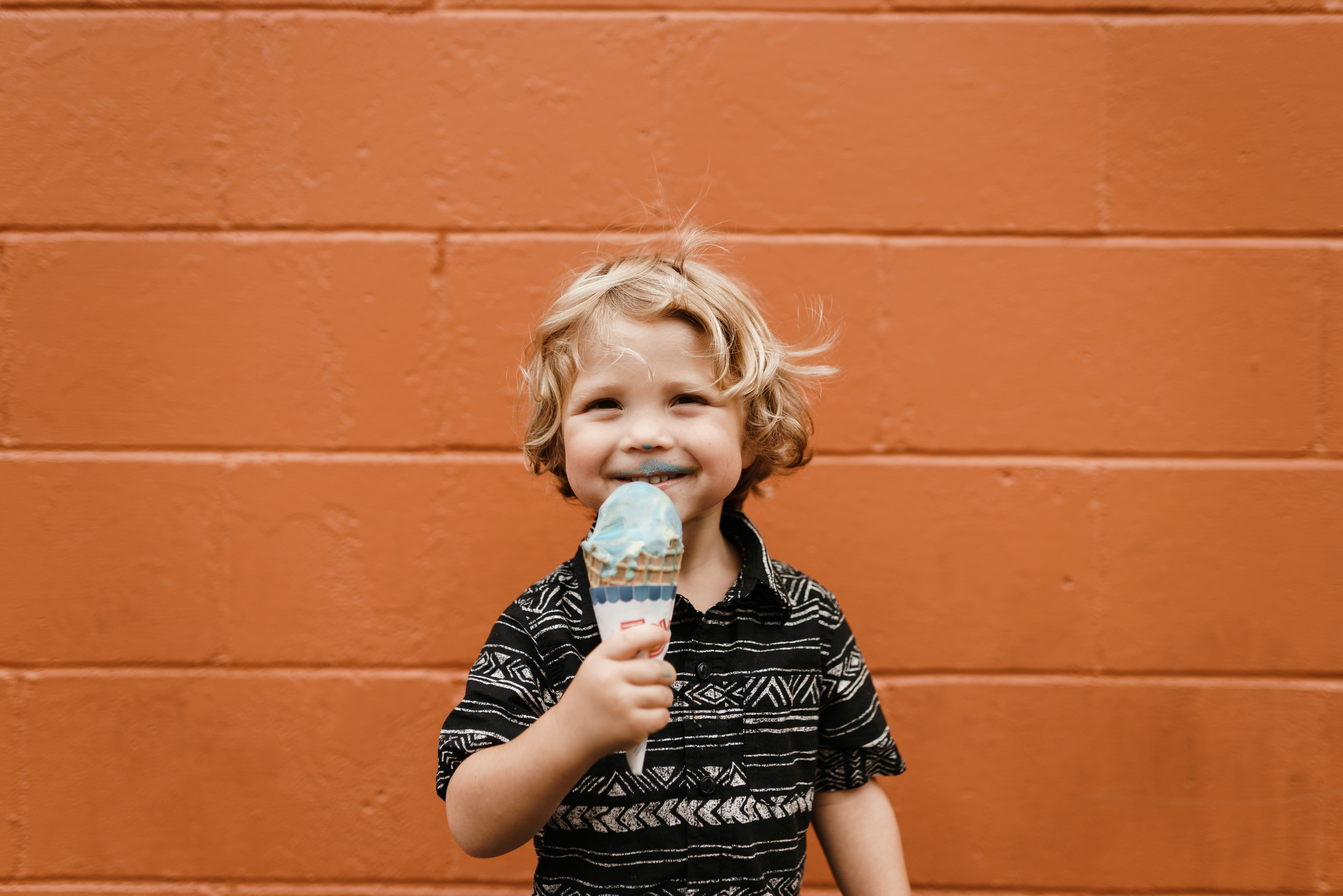 A little boy wearing a printed black and white shirt with ice cream all over his face and an ice cream cone in his hand in Bentonville