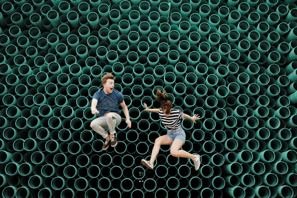 minimalist photography of man and woman jumping in front of tube wall