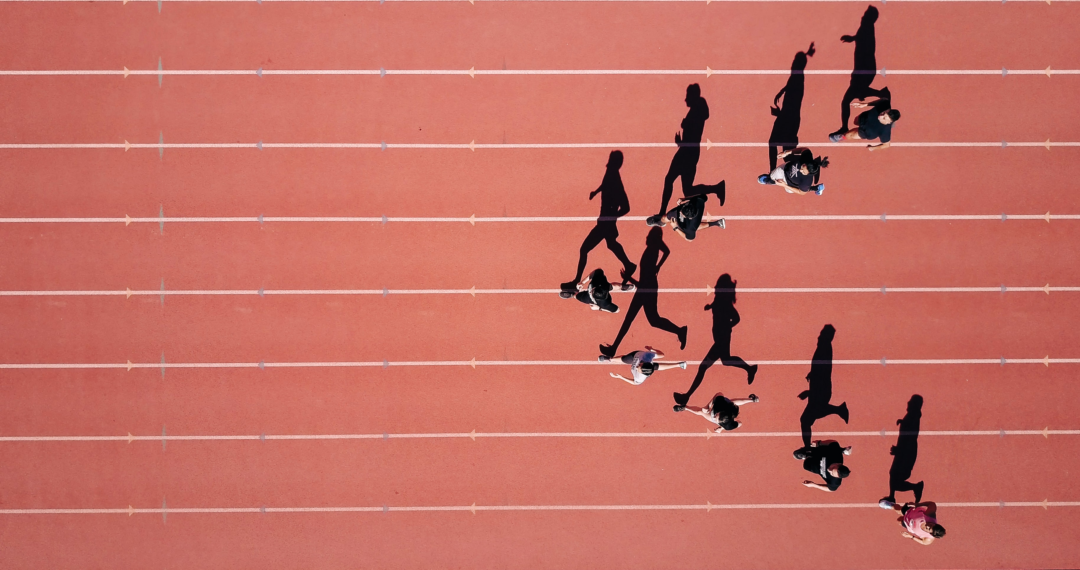 A drone shot of runners casting long shadows on the red track