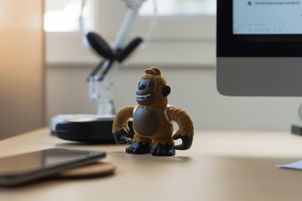 brown monkey toy near black smartphone