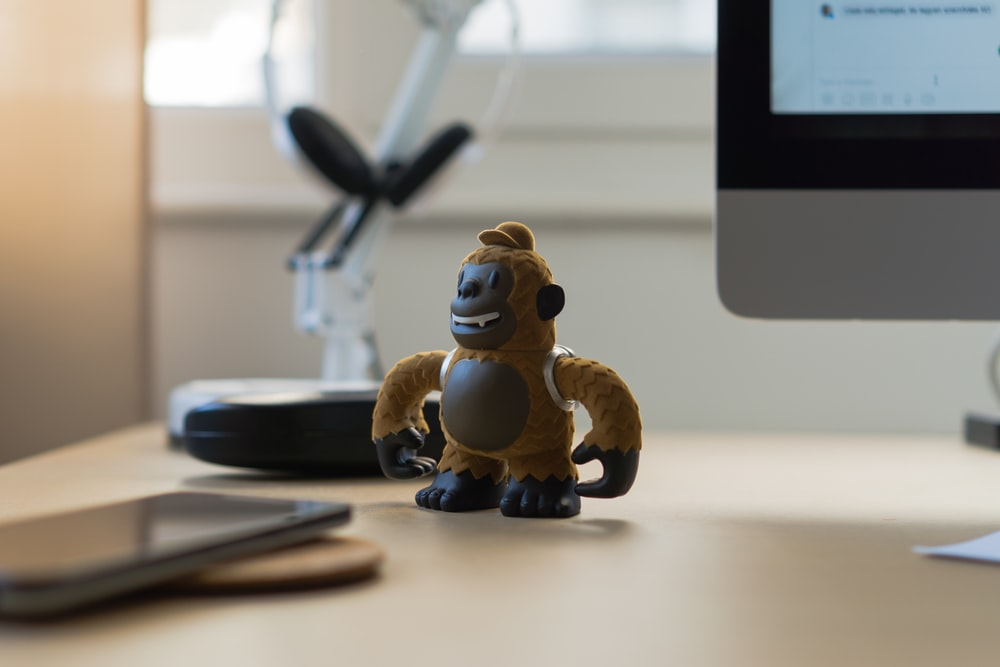 brown monkey toy near black smartphone