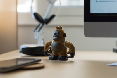 brown monkey toy near black