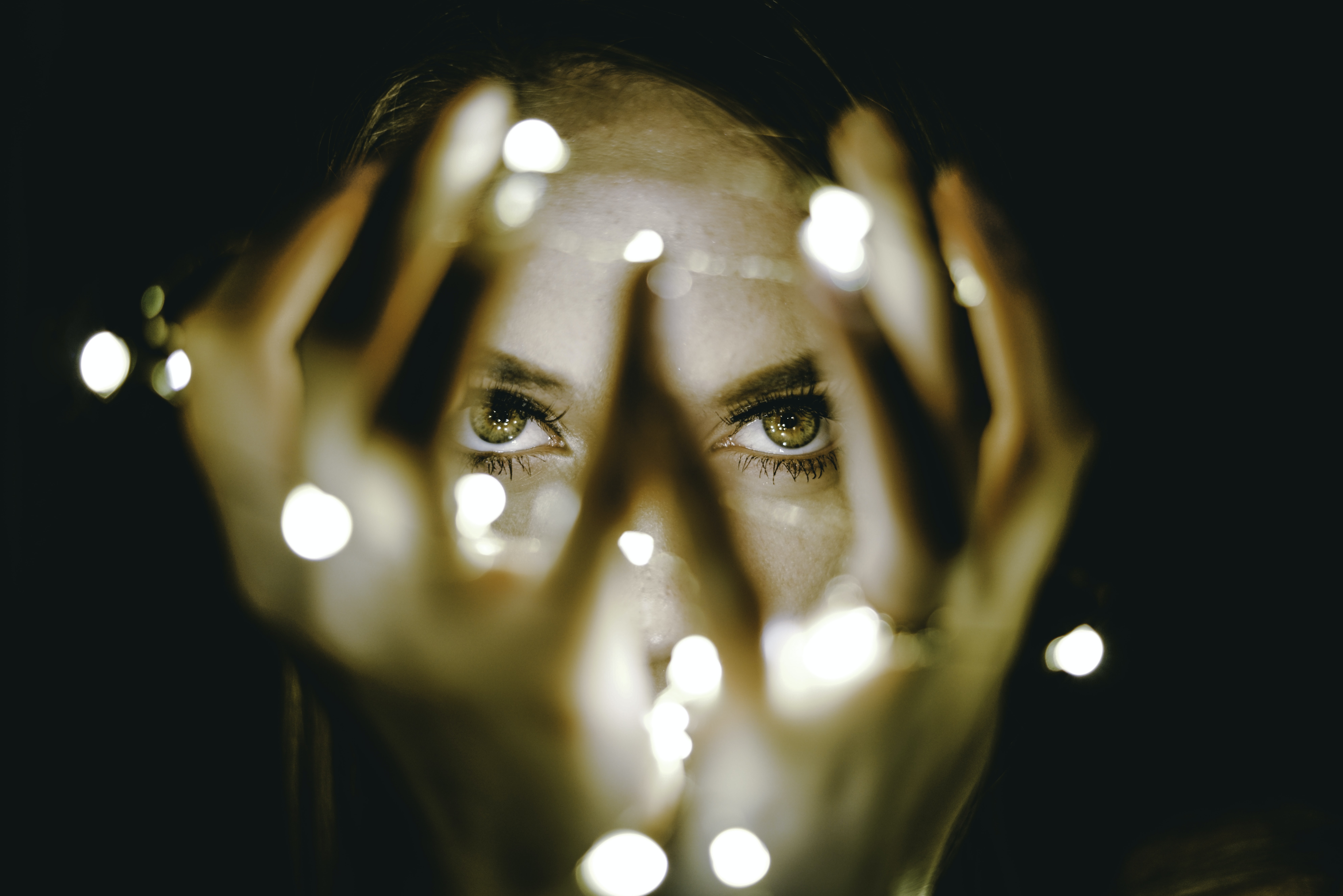 A close-up of woman's eyes through her hands surrounded by fairy lights.