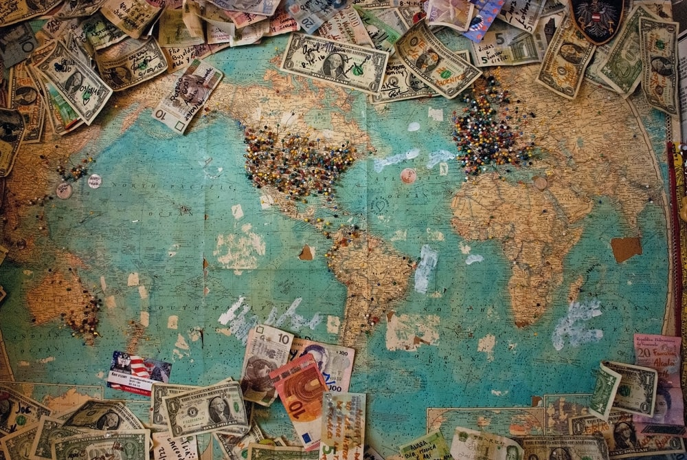Various currency bills pinned to a large world map with colorful pins in various locations