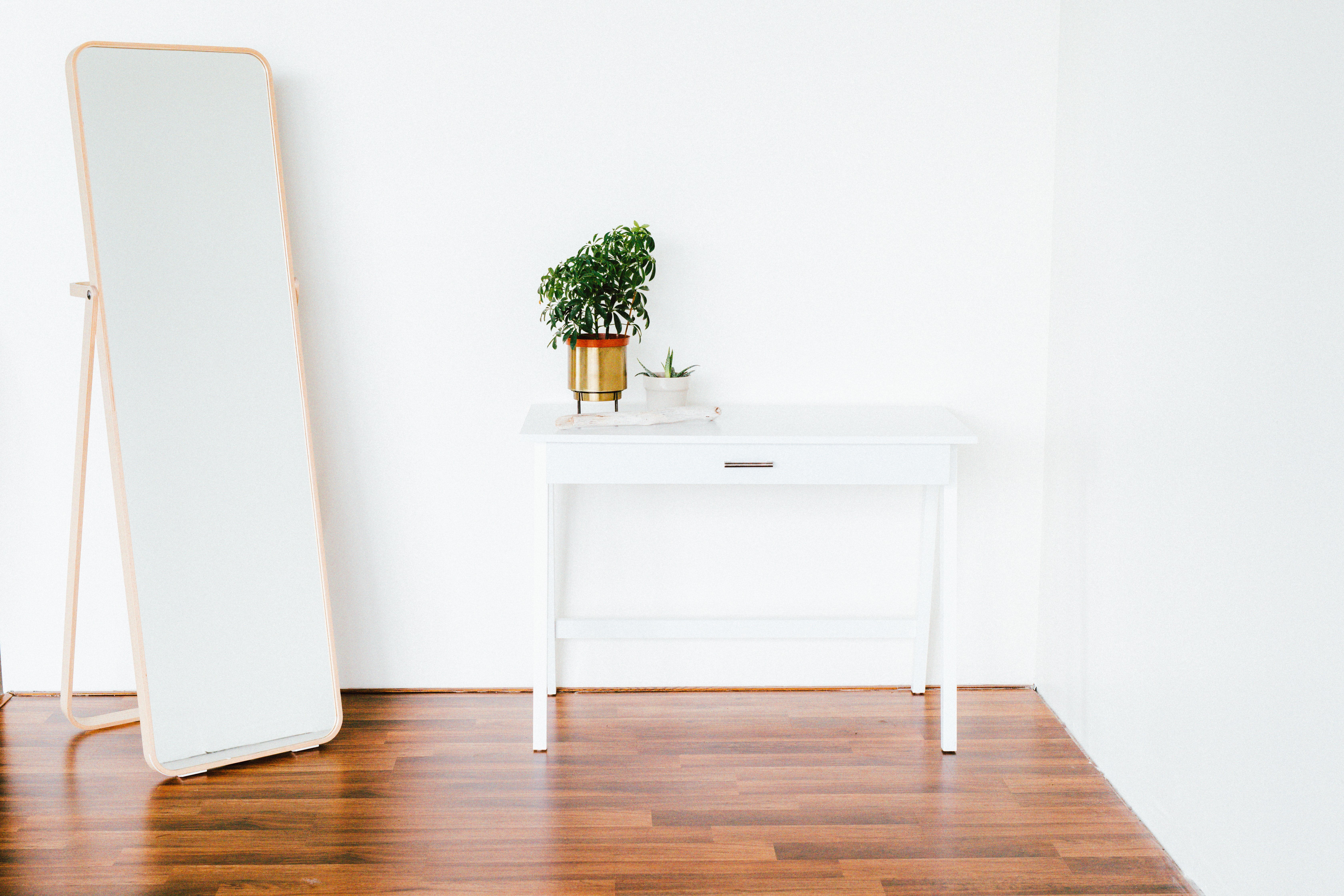 White room interior with hardwood floor with a desk, plant, and full-length mirror