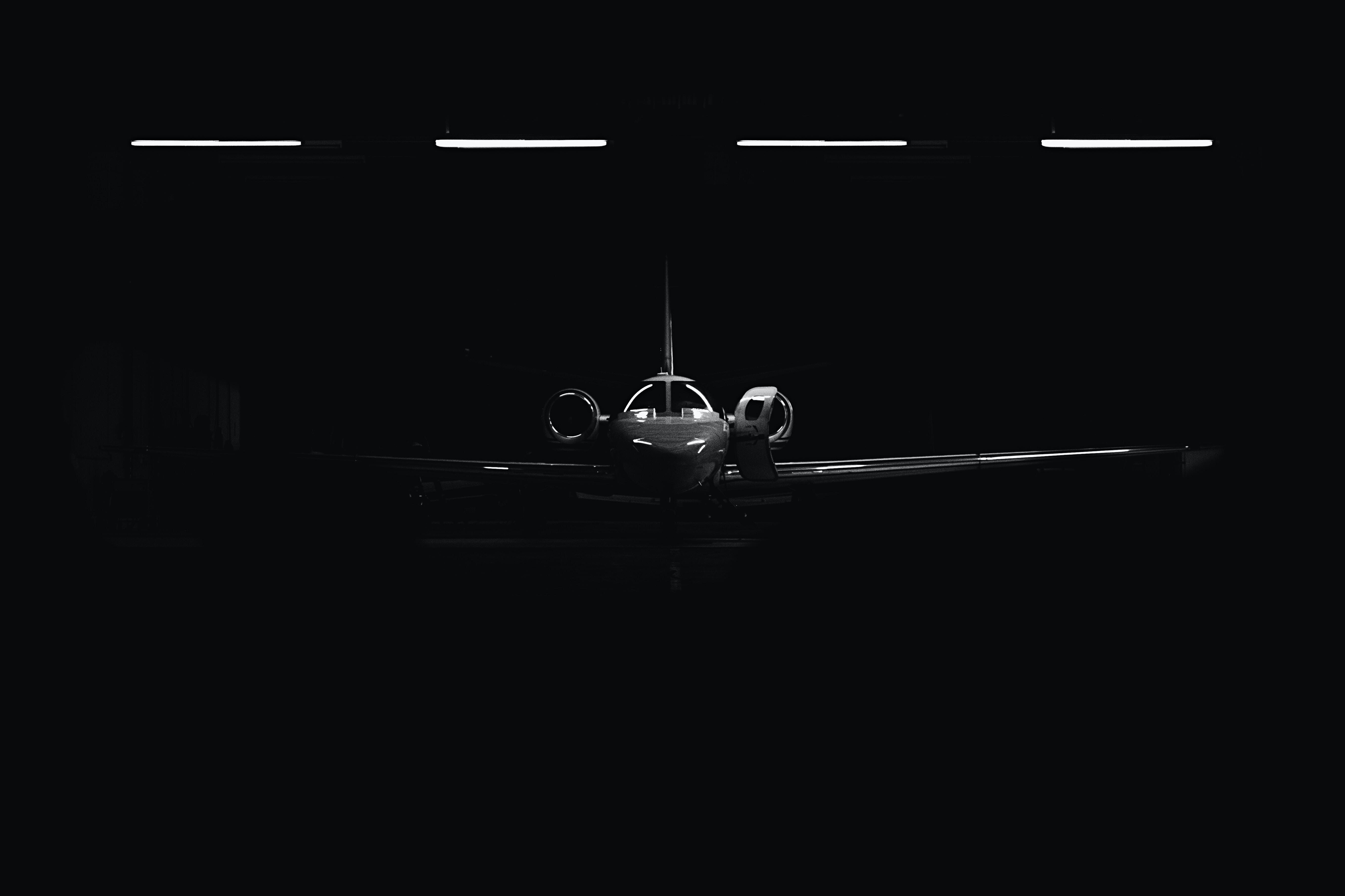 A dim shot of a glossy airplane in a dark hangar