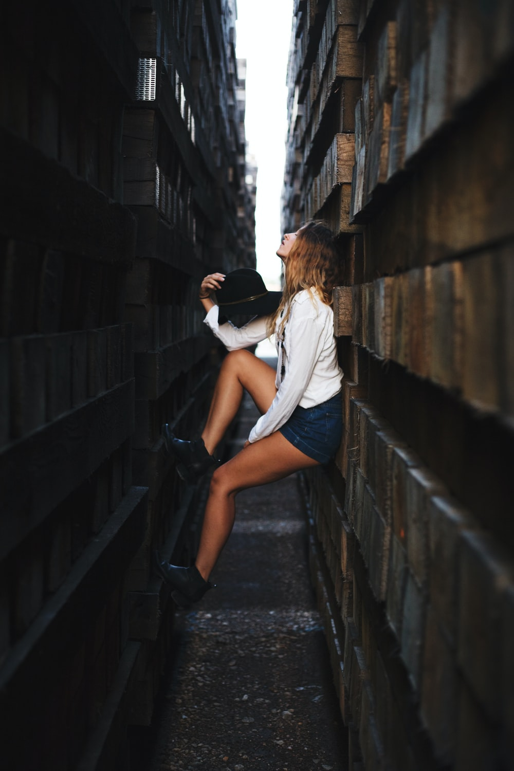 woman holding her hat leaning on brick wall