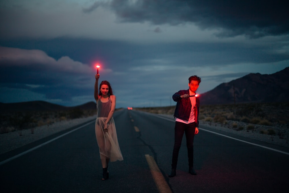 man and woman holding red flare on yellow line road