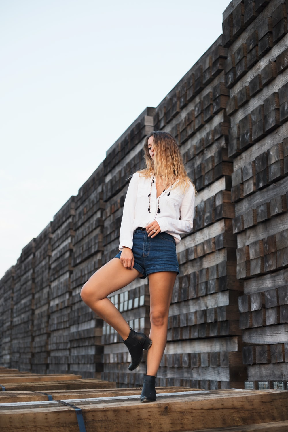 woman in white dress shirt and blue denim shorts