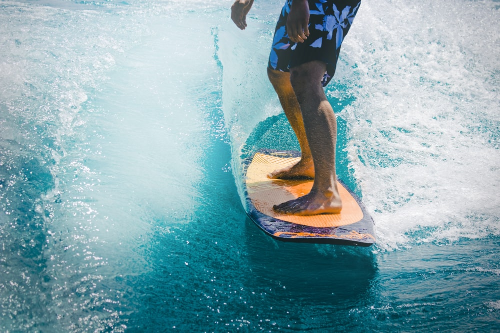 man riding wave with orange surfboard