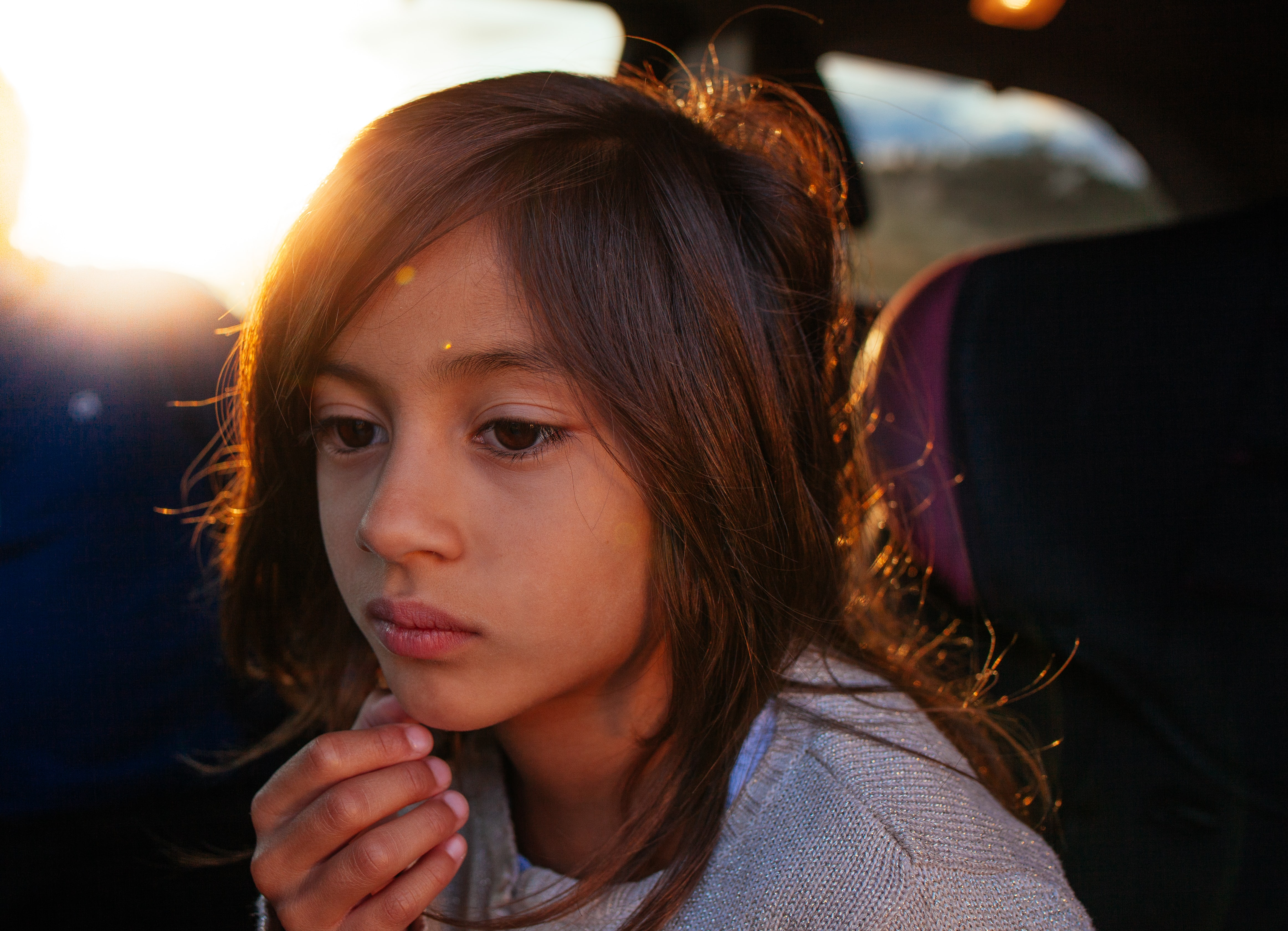Sad young child sitting in a car alone