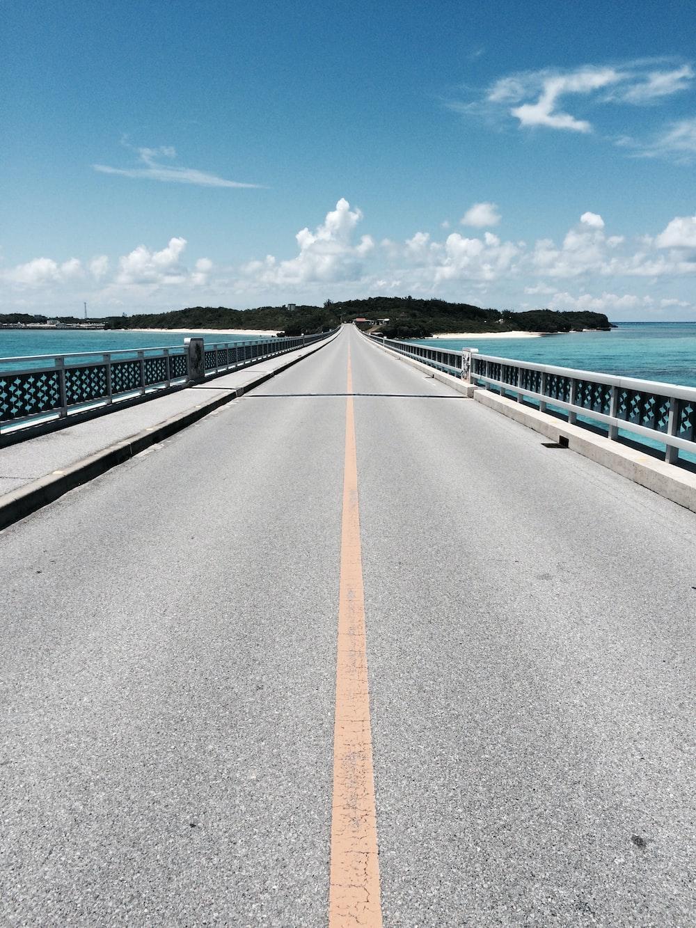 asphalt road near mountain under blue and white cloudy sky