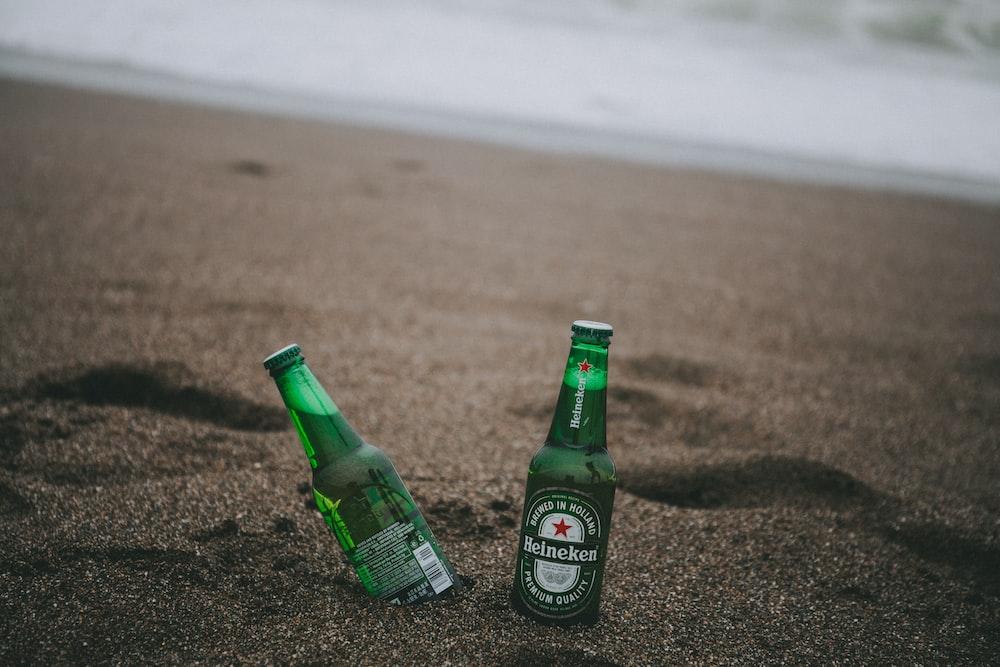two green Heineken bottles on gray soil
