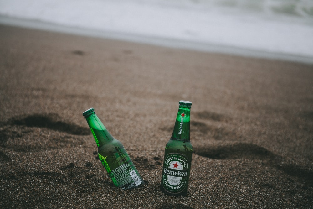 two green Heineken bottles on gray soil