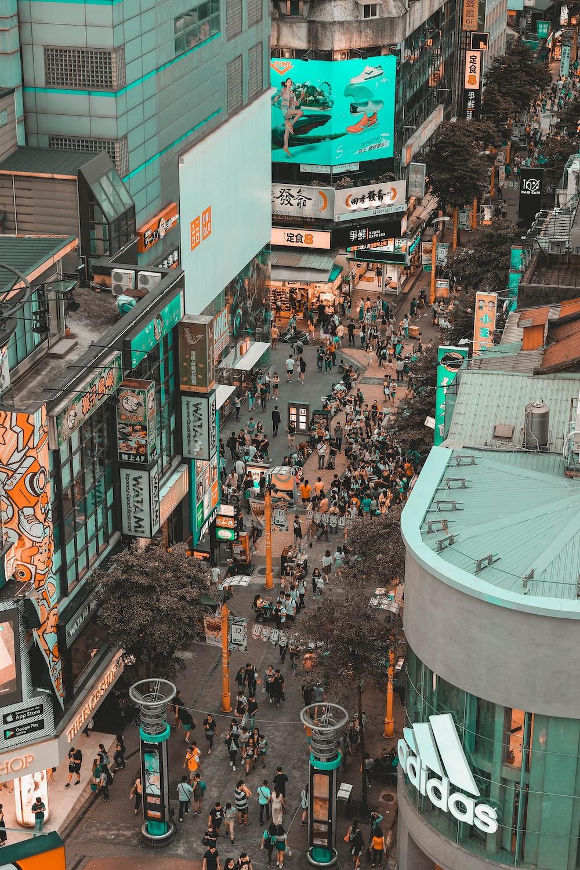 aerial photography of people walking on street between buildings