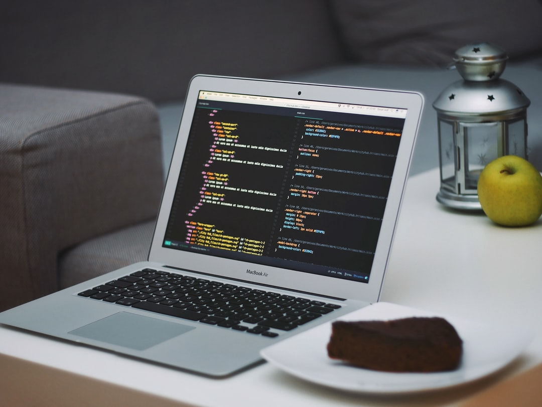 Open laptop on coffee table displaying coding beside chocolate cake in living room with couch