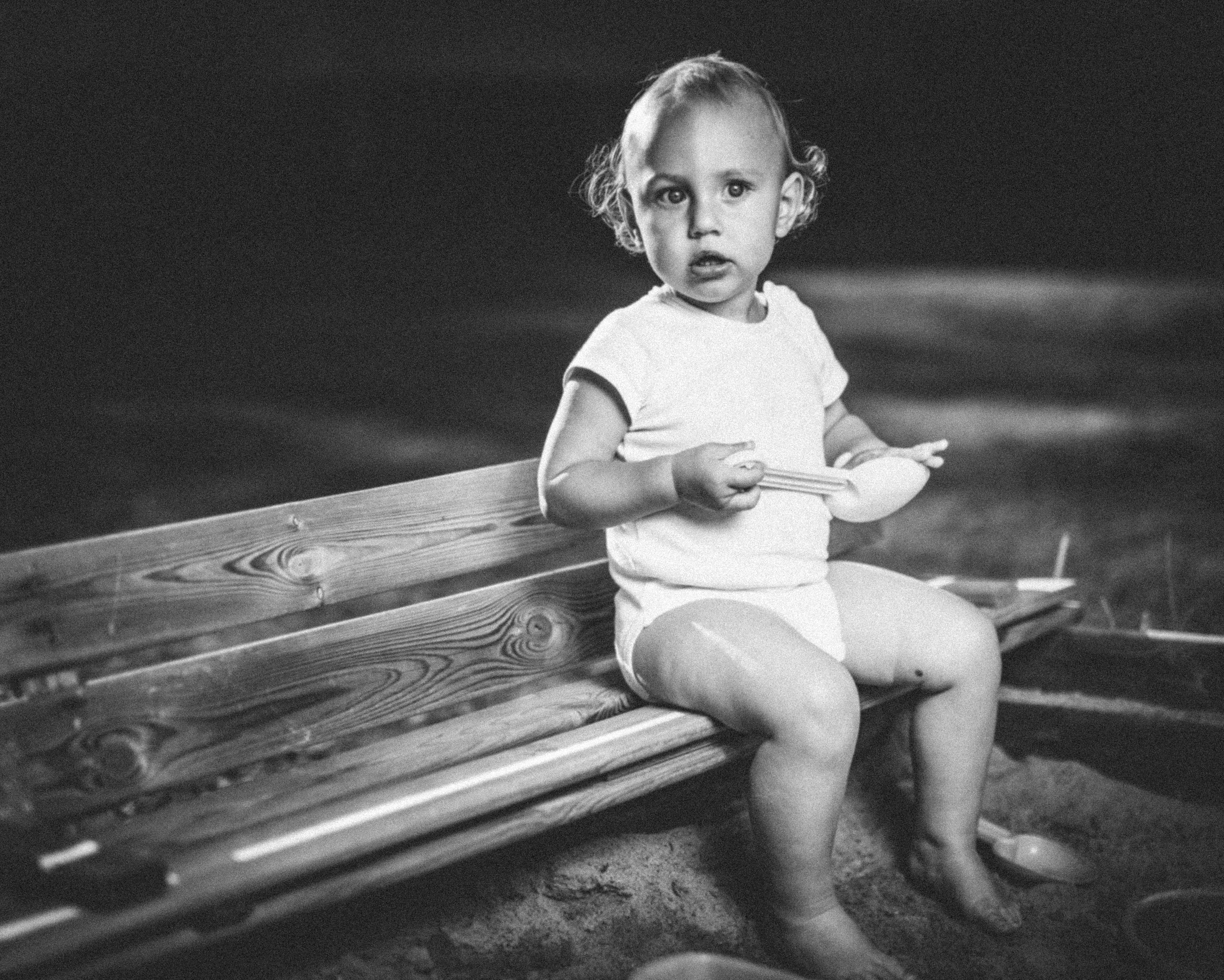 grayscale photography of toddler sitting on benchg