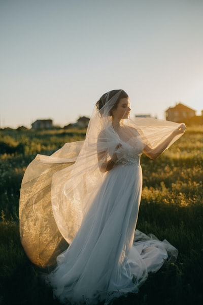 Bride standing in a field in a wedding gown wth a veil wrapped around her