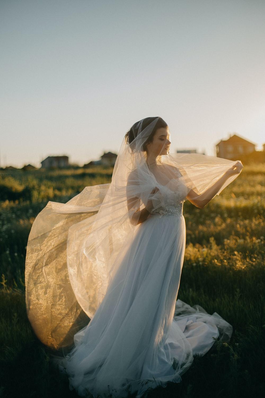 woman wearing wedding gown in green grass field