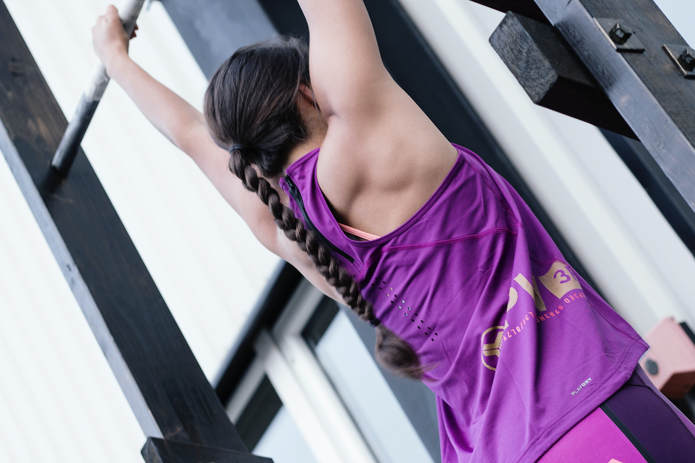 A woman with a braid in athletic clothing hangs from a metal pull-up bar