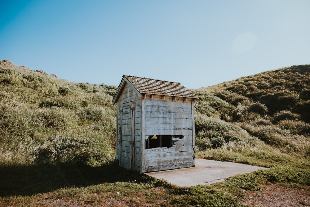 shed on grass field under cumulus clouds