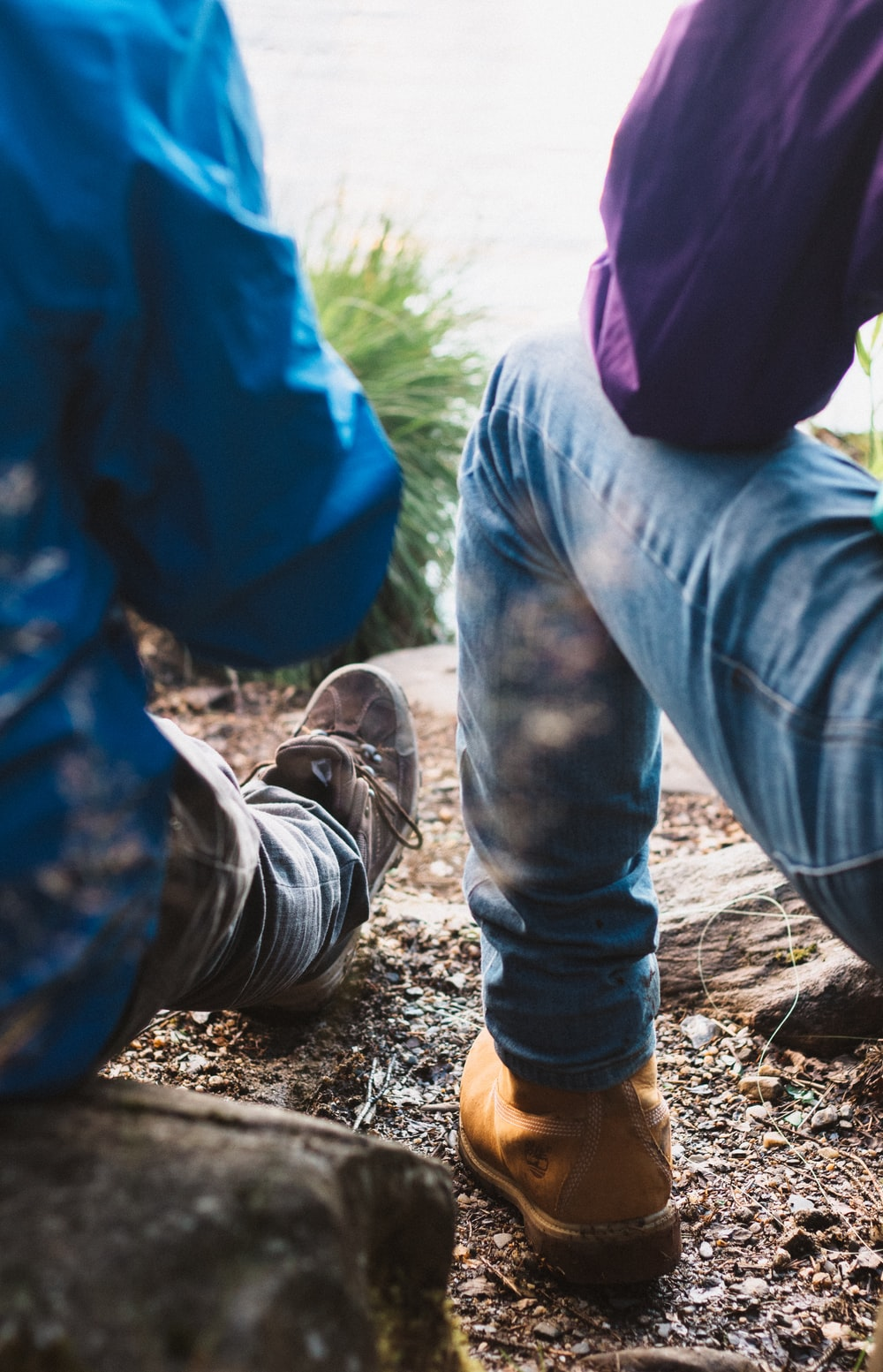 two person sitting on rock wearing blue denim jeans photo