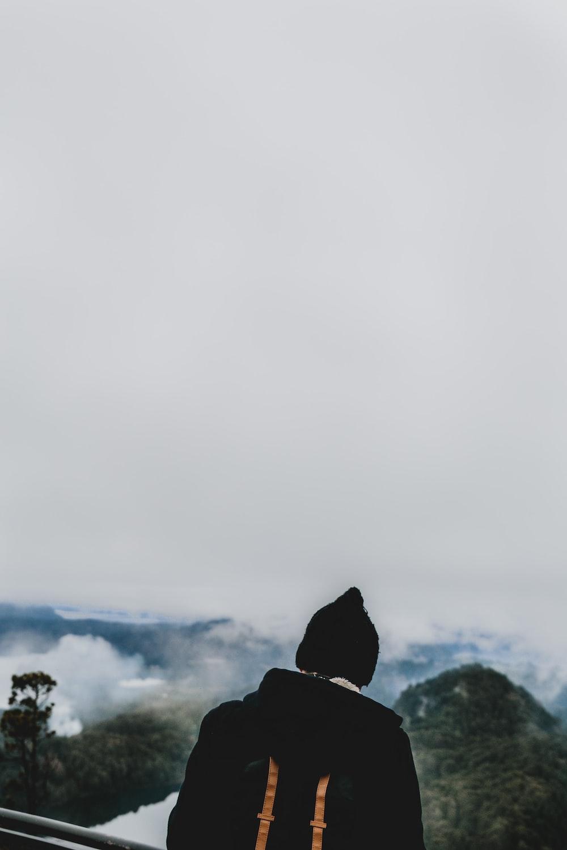 man wearing black jacket and knit cap facing green mountains