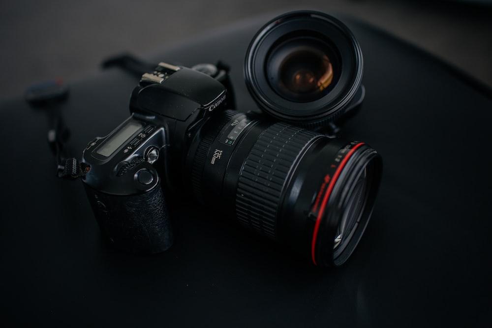black Canon DSLR camera beside camera lens