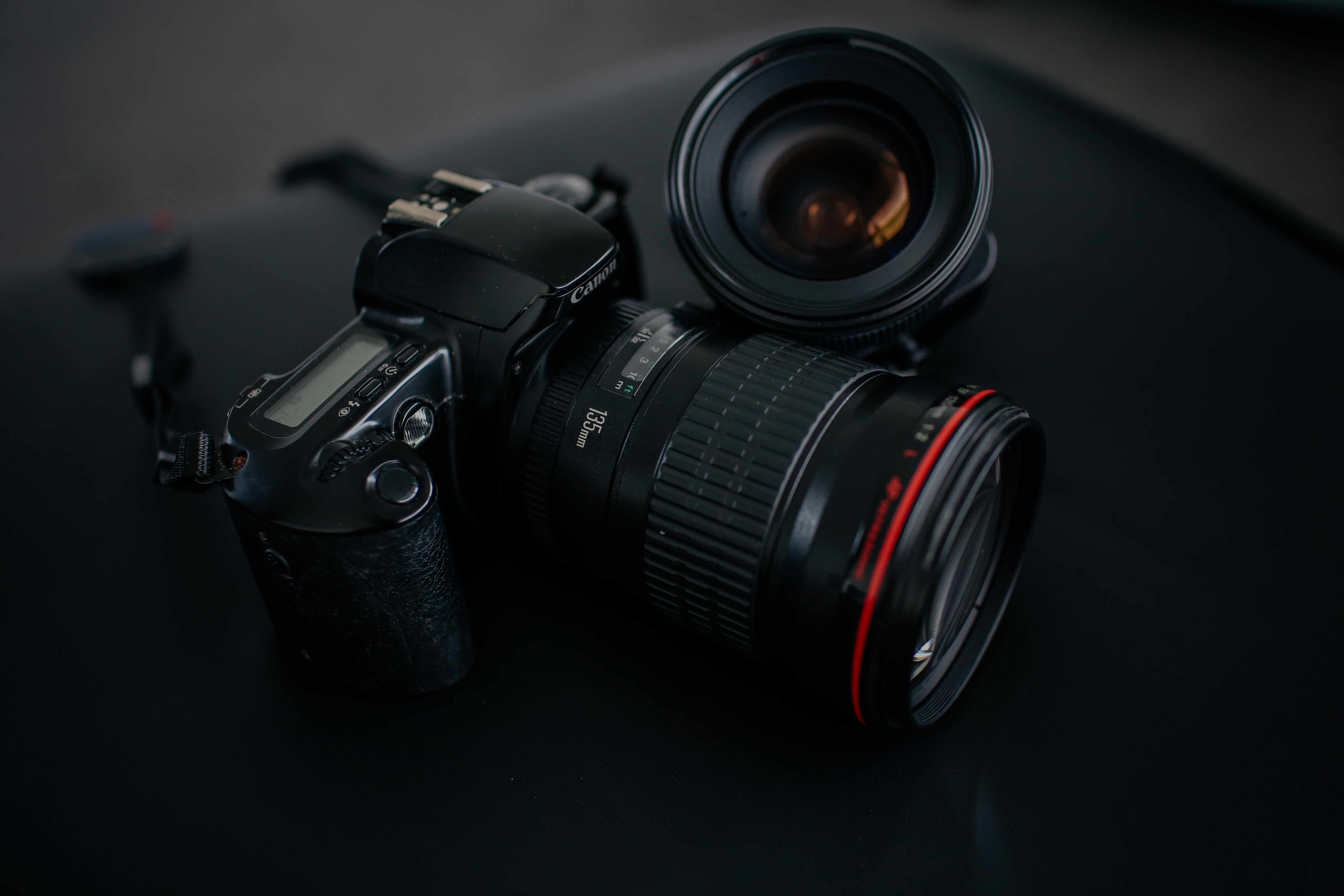 black Canon DSLR camera beside camera lens