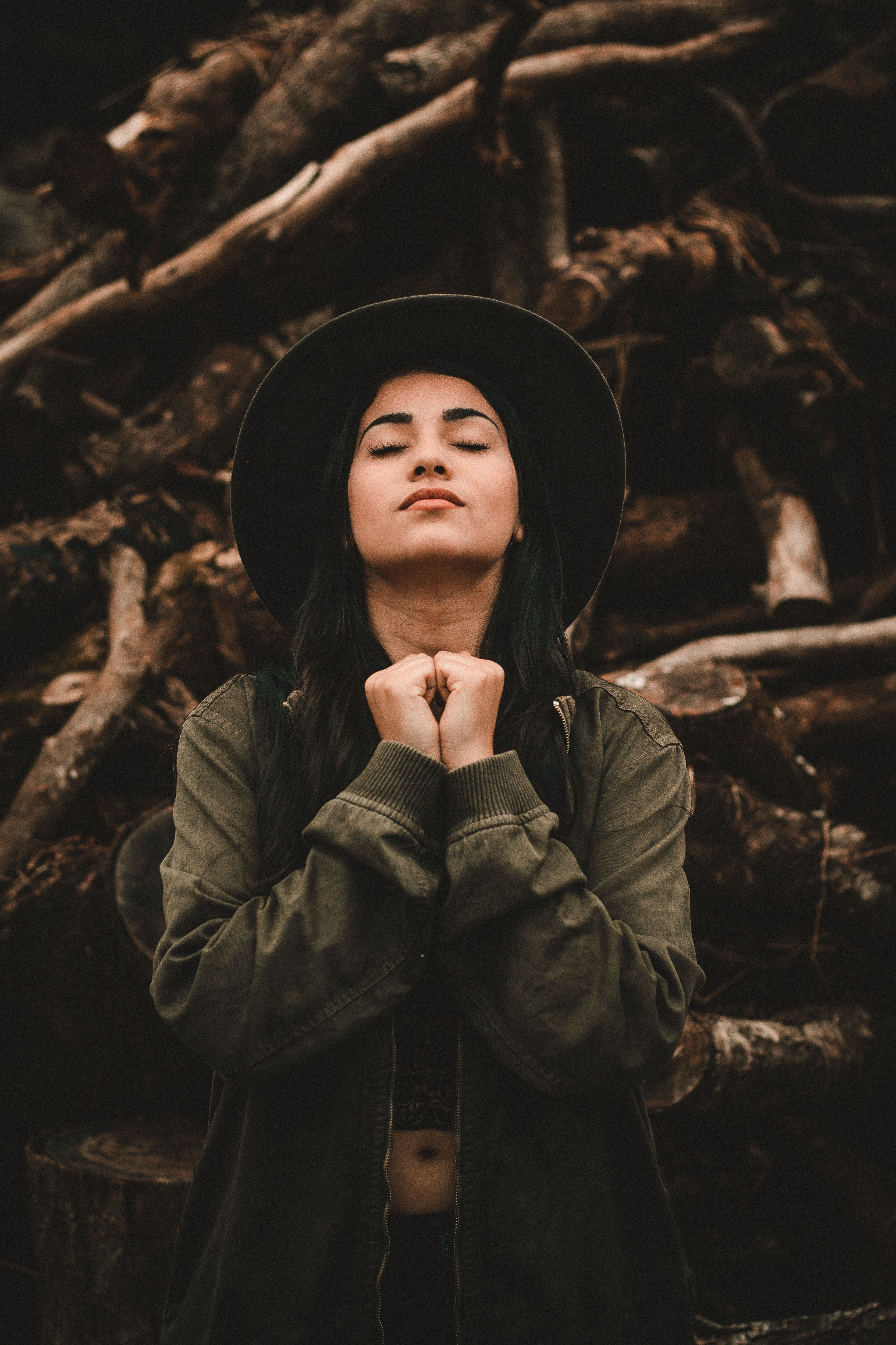 woman closing her eyes near pile of logs
