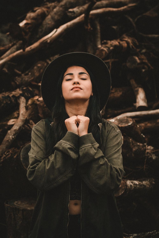 woman closing her eyes near pile of logs