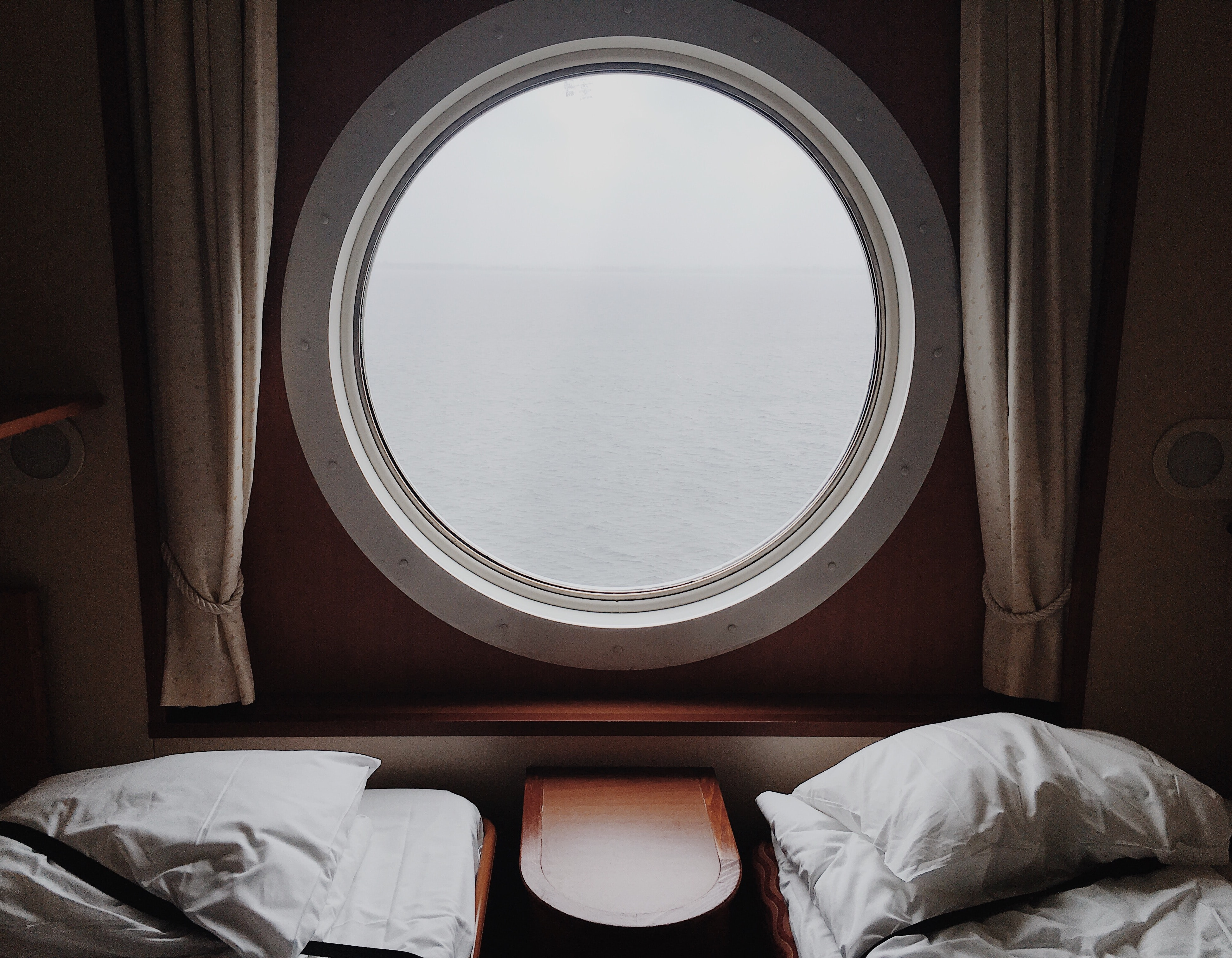 Two beds with pillows on either side of a circular window with curtains overlooking water