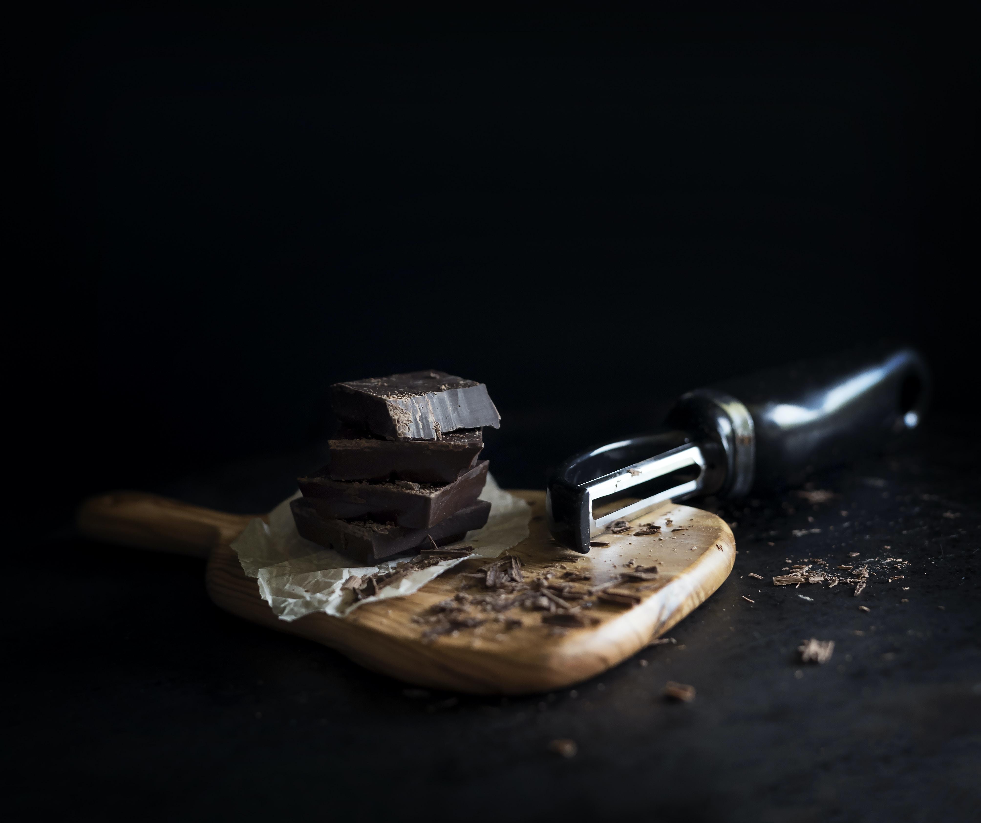 Food peeler shreds blocks of dark chocolate on a cutting board