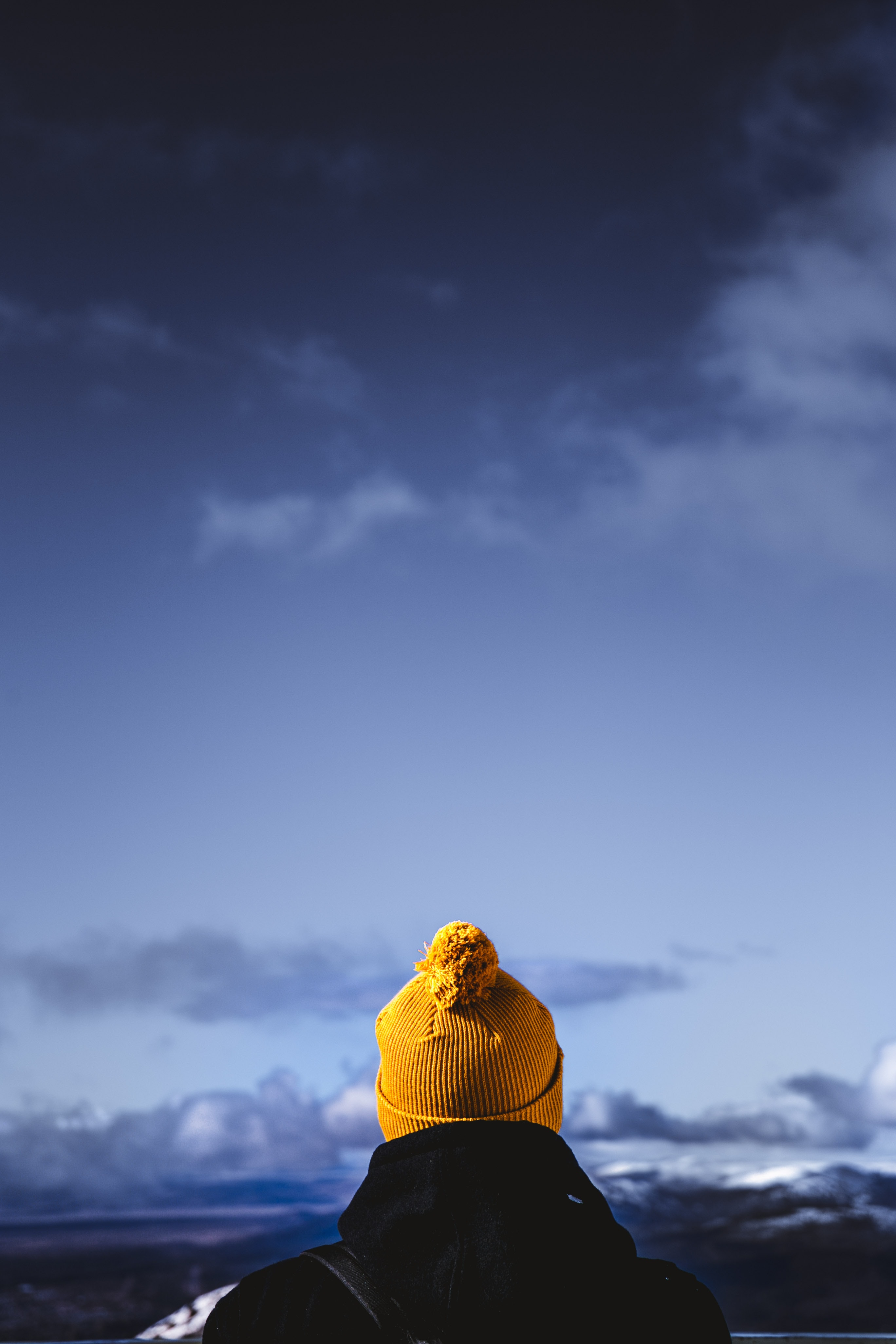 person wearing brown bobble hat facing cloudy skies