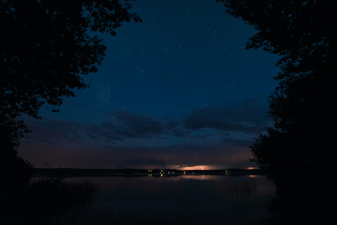 We were camping on Thunder Lake Alberta taking photos of the night sky. We were lucky enough to catch a bit of a thunder storm. In order to have still stars and a long enough exposure to capture some lighting I had to merge two photos. Cheers!
