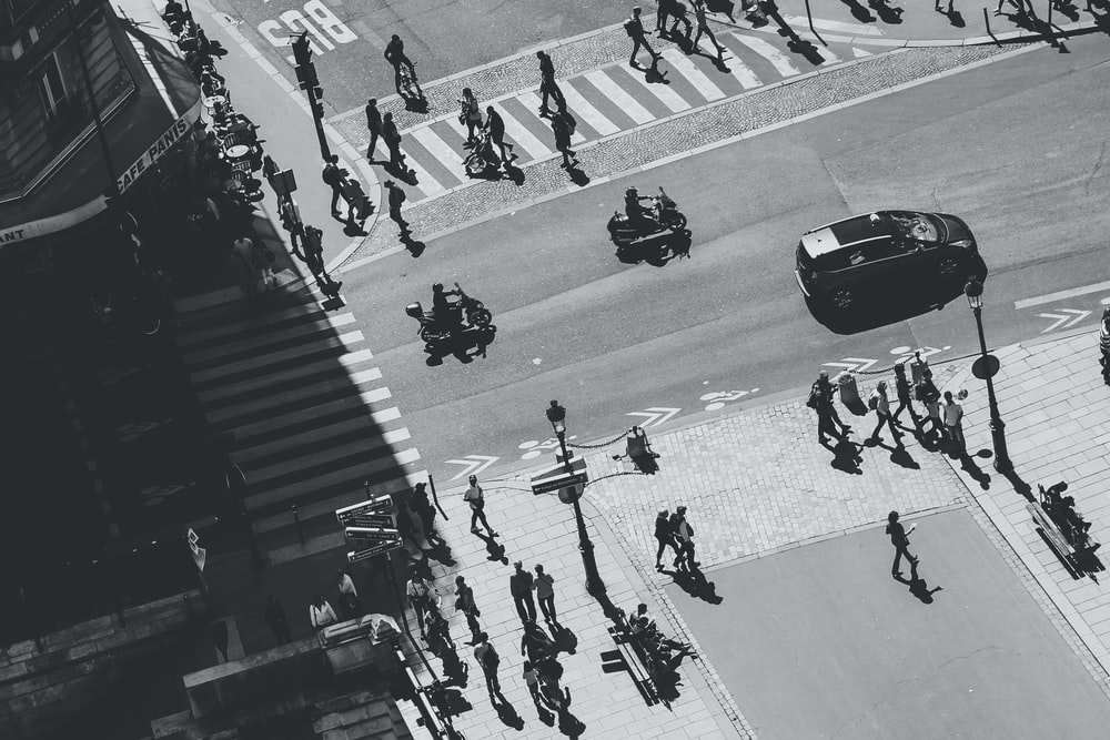 grayscale photography of group of people crossing streets
