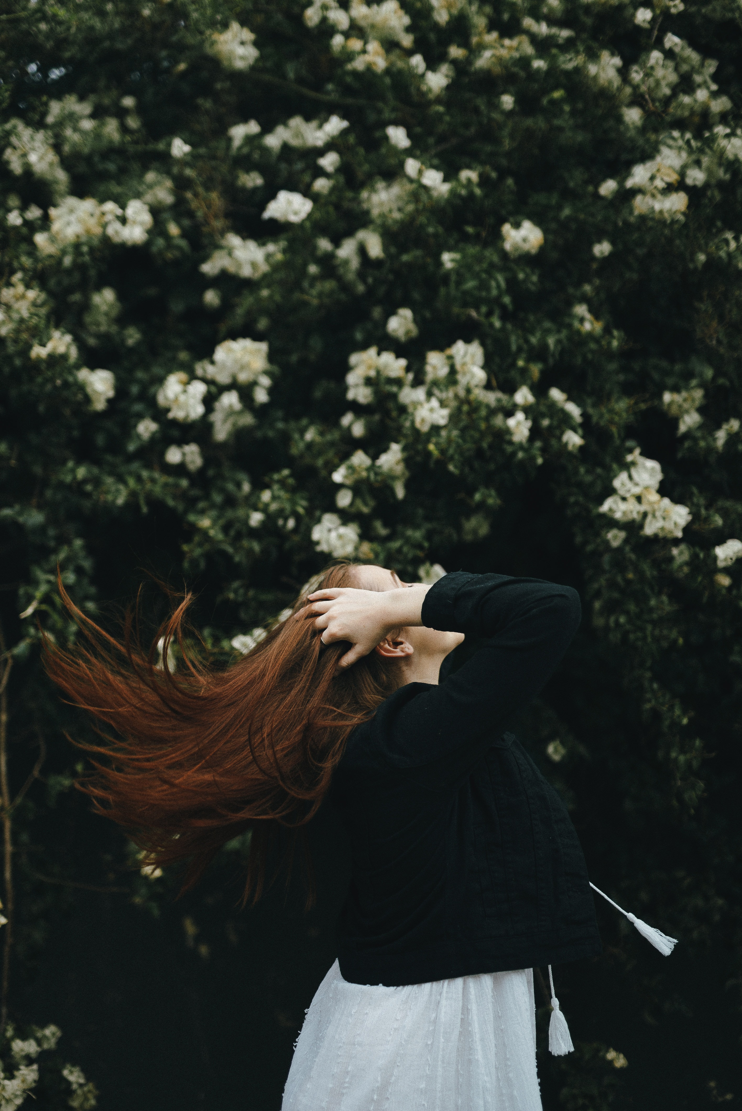 woman holding her hair near bougainvillea plant