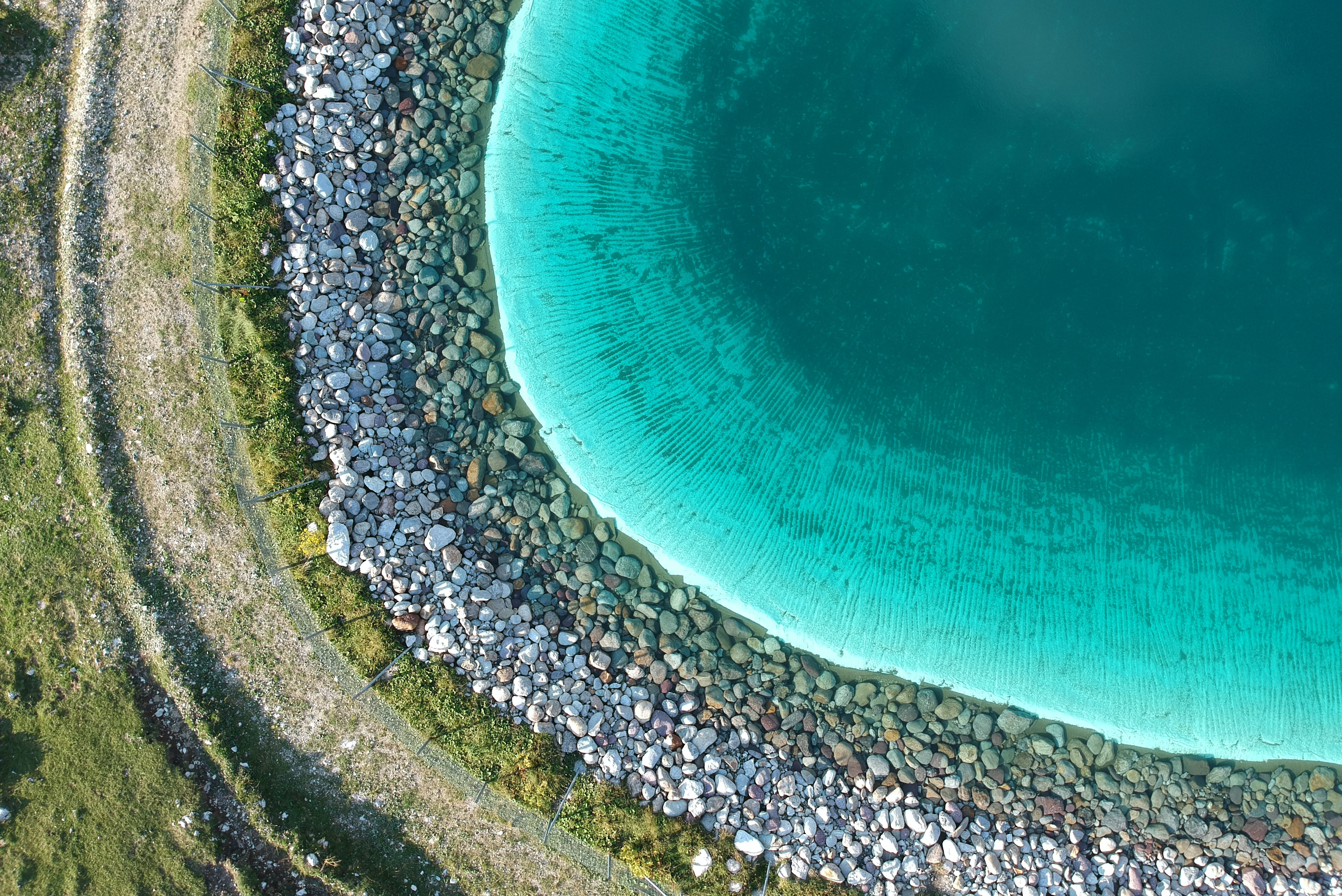 aerial photography of body of water surrounded with stones during daytime