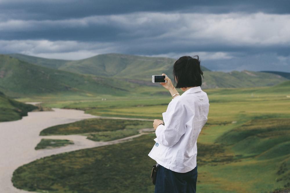 woman taking a photo of mountain