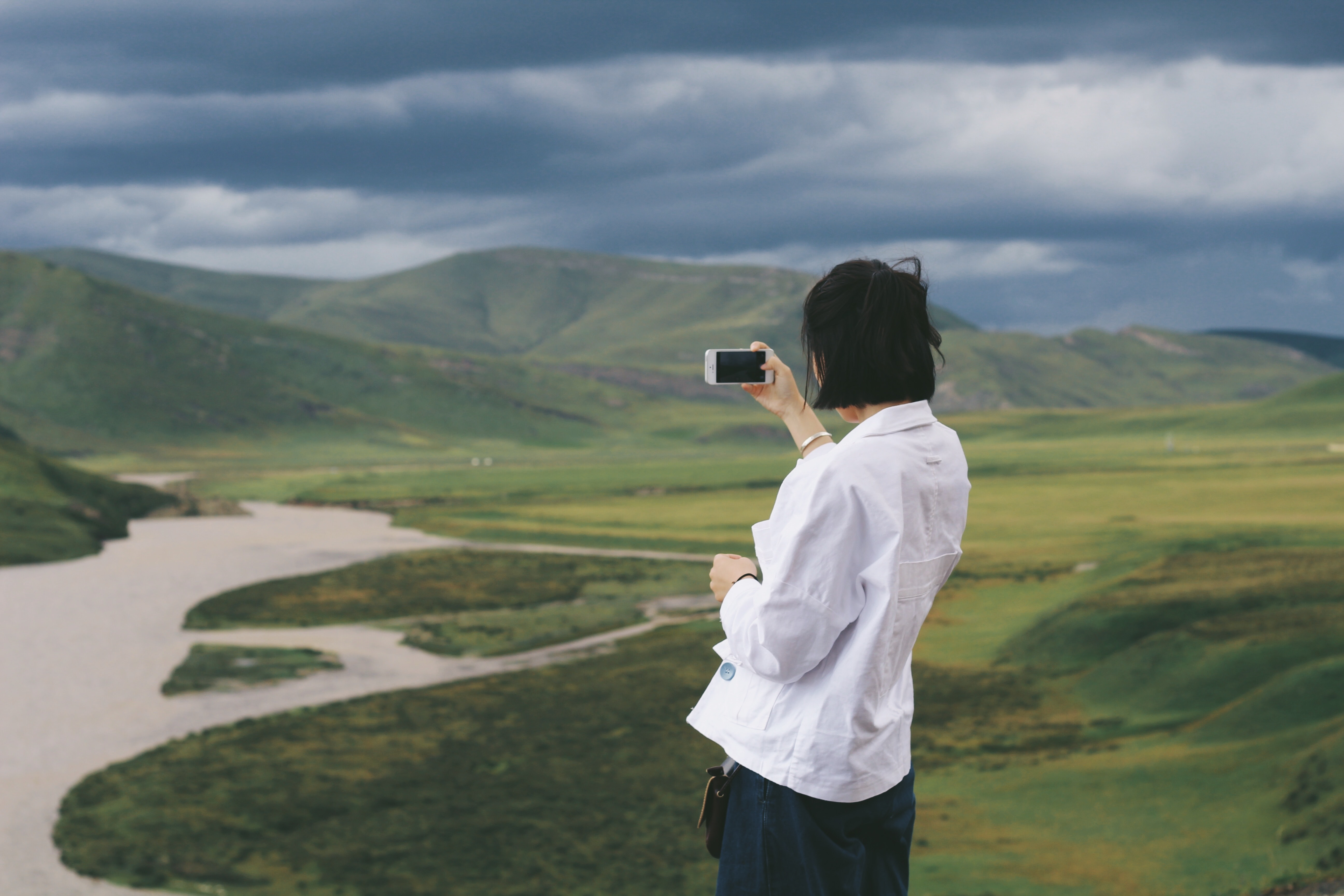 Person in white shirt using a smartphone to photograph green hills and river