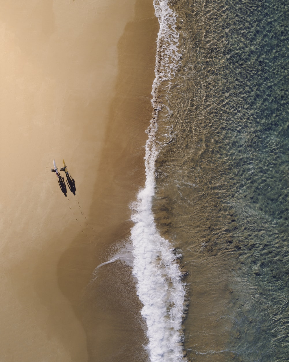 aerial photography of two persons walking along seashore during daytime