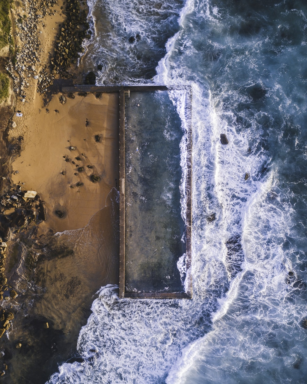 aerial photography of sea hitting sand at daytime