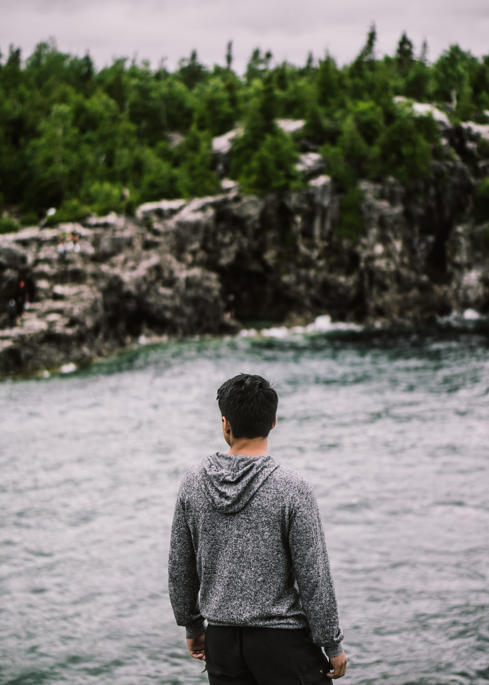 man facing backward fronting body of water and trees foliage
