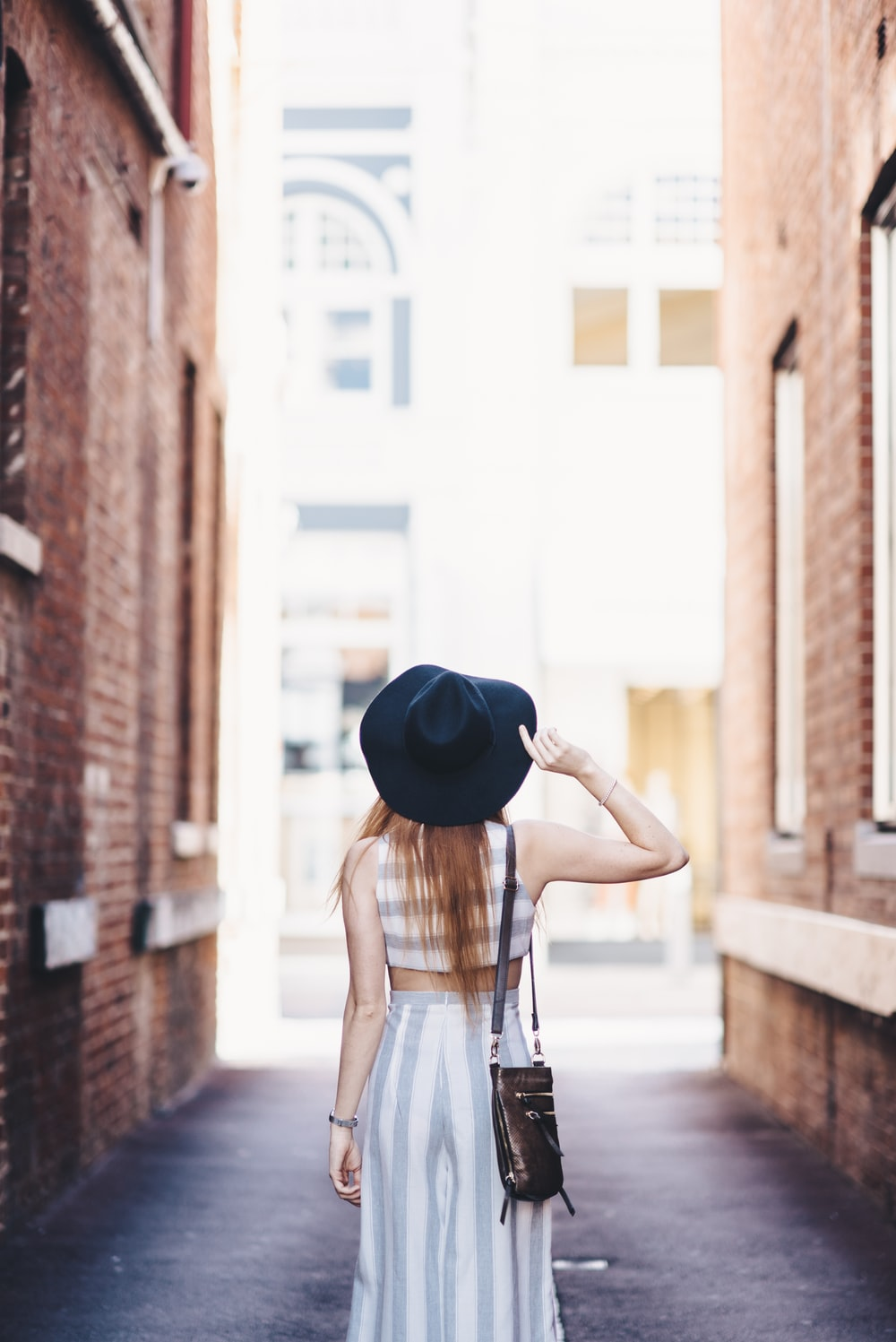 woman standing on pathway holding hat