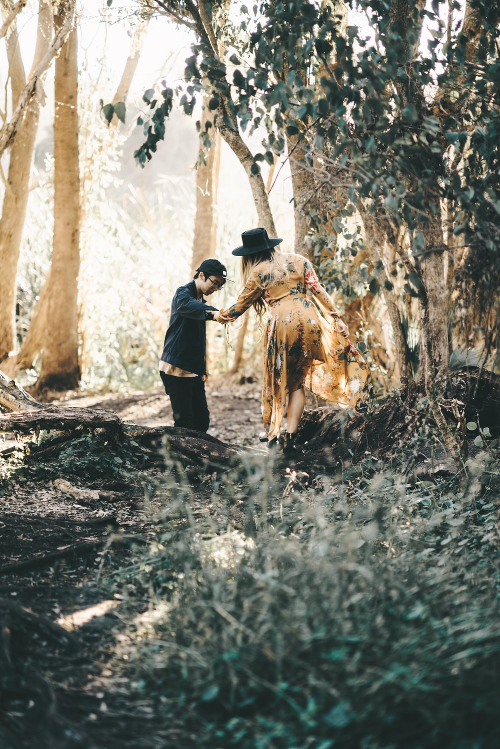 man helping woman cross tree trunk