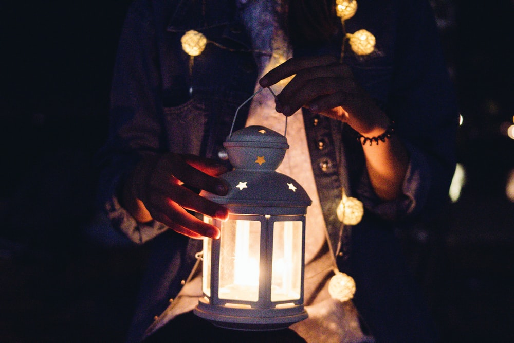 person holding candle lantern