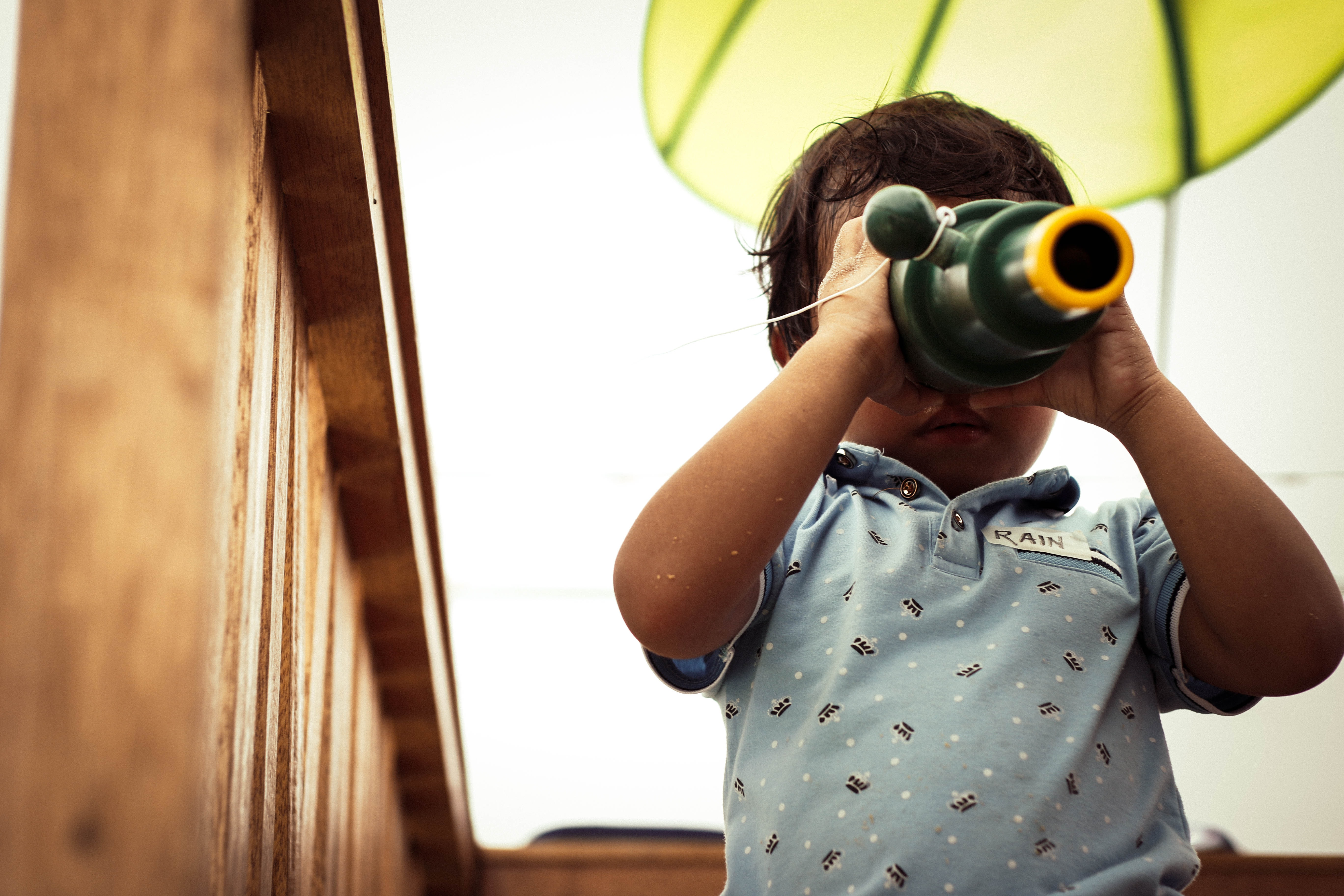 """Infant wearing baby blue shirt with a name tag that says """"RAIN"""" using a telescope looking down the wide lens while stringed to a wooden handrail"""
