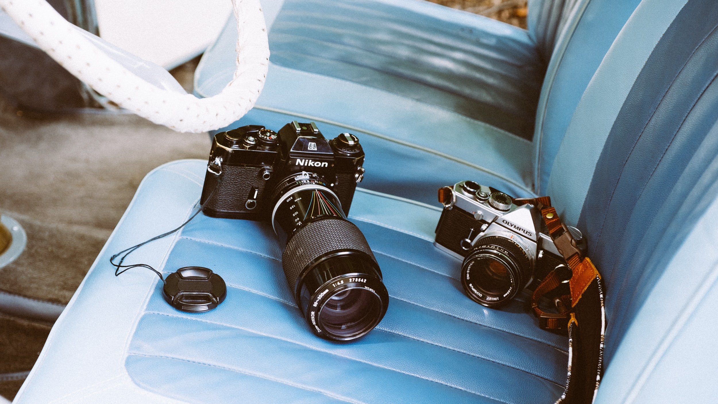 Photographer's Nikon and Olympus cameras on a car seat