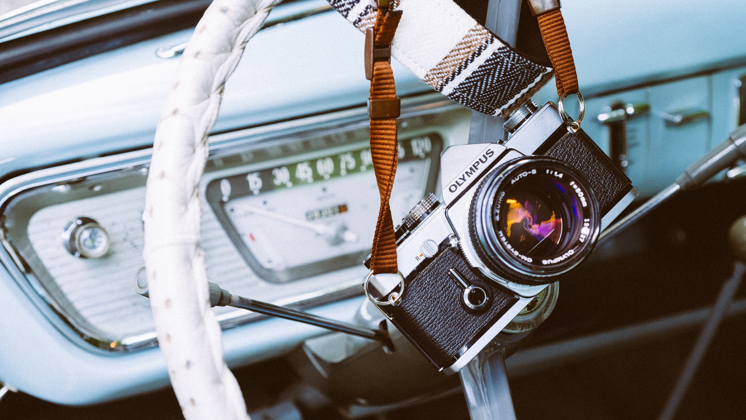Olympus camera and strap on top of a white steering wheel in a vintage car