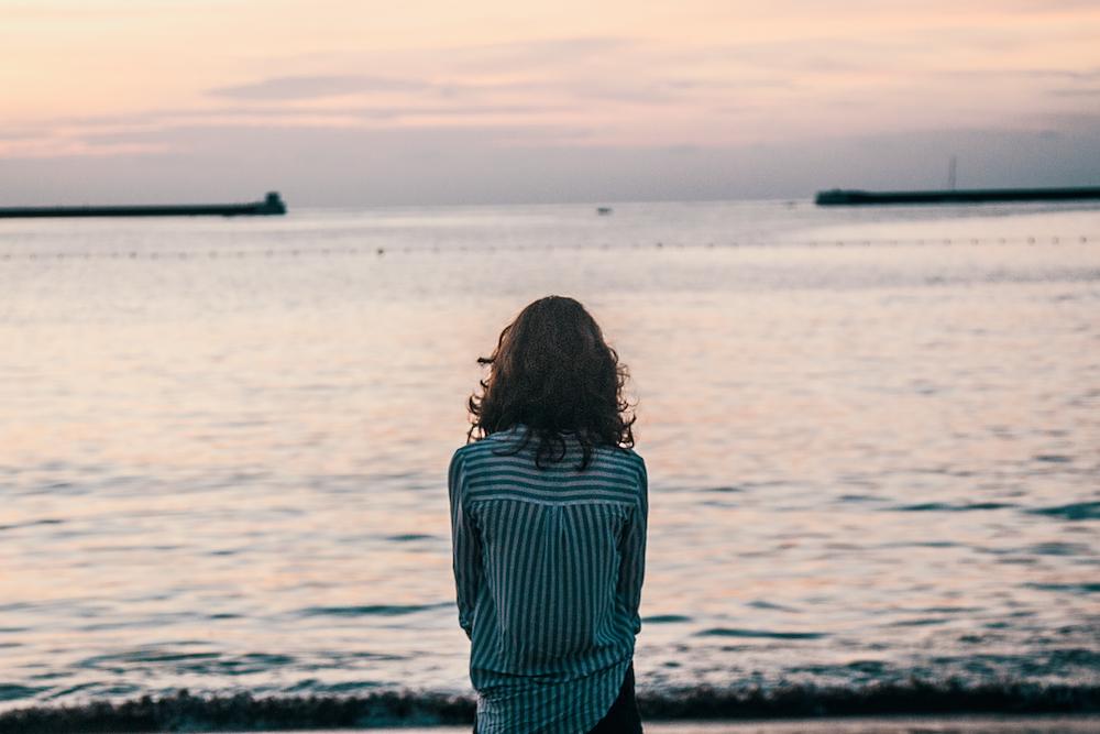 woman in front ocean water under white sky